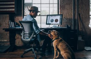 man sitting on rolling chair holding dog